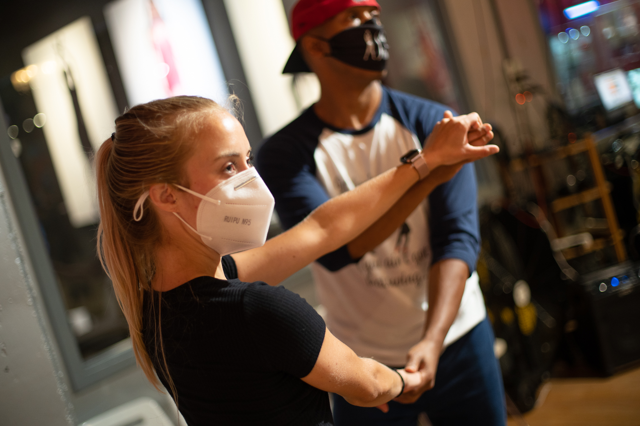 Salsa students take a class at the Salsa With Silvia dance studio while wearing masks during COVID-19